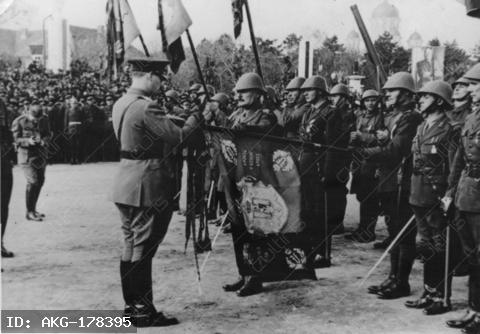 Michael I, King of Romania 1927-30 as guardian and 1940-47, (born 25.10.1921)-Celebration in Bucharest for the Romanian forces fighting alongside the Germans, 8 November 1941: King Michael I decorates the regimental flags.-Photo.